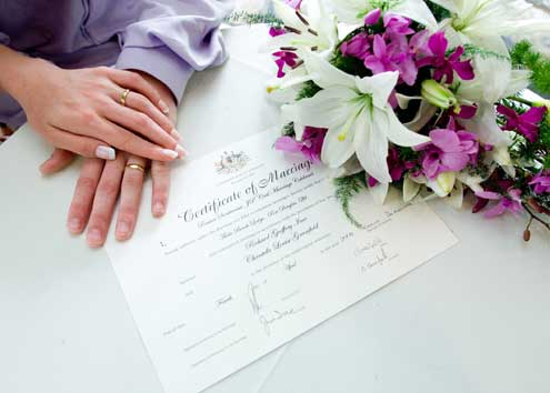 hands on top of wedding certificate